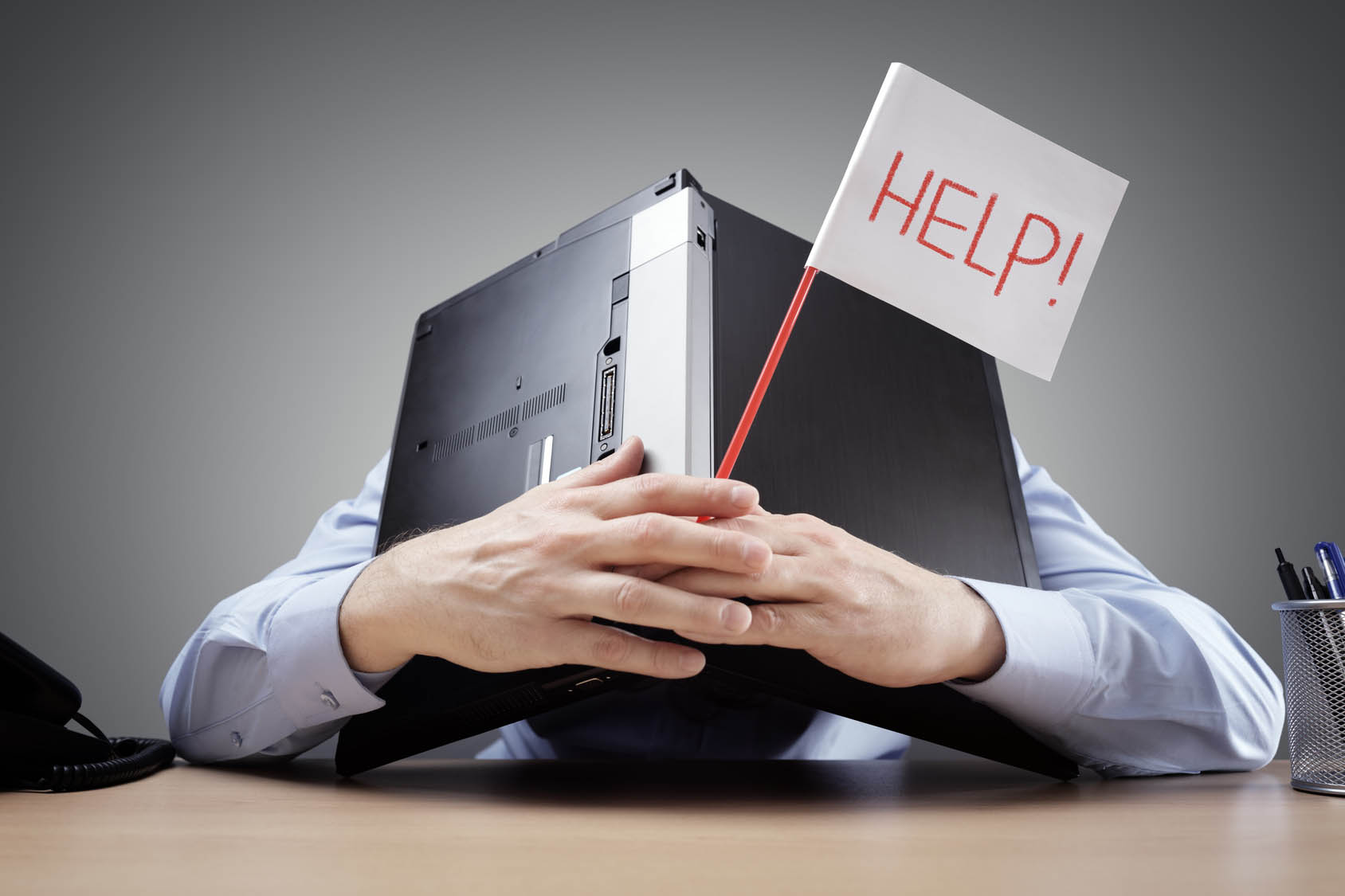 Frustrated and overworked businessman burying his head under a laptop asking for help