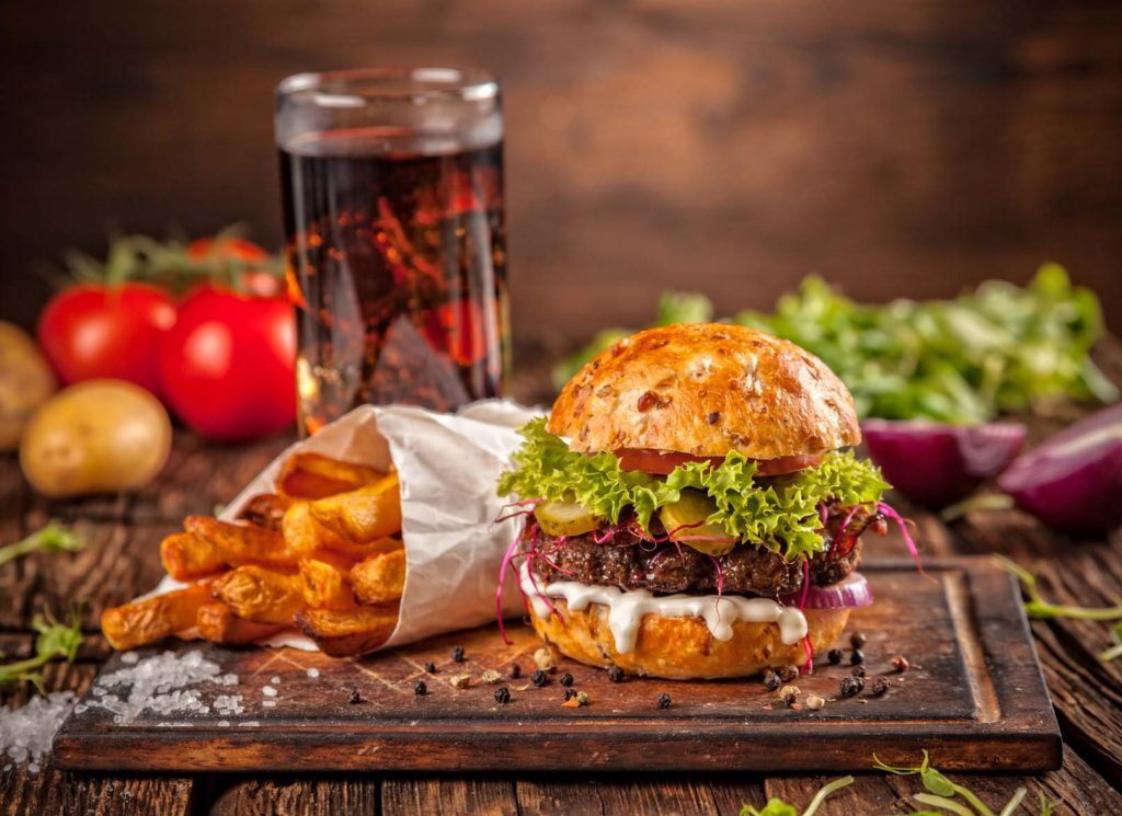 Fresh home-made hamburger served on wooded table with steak fries and cola drink