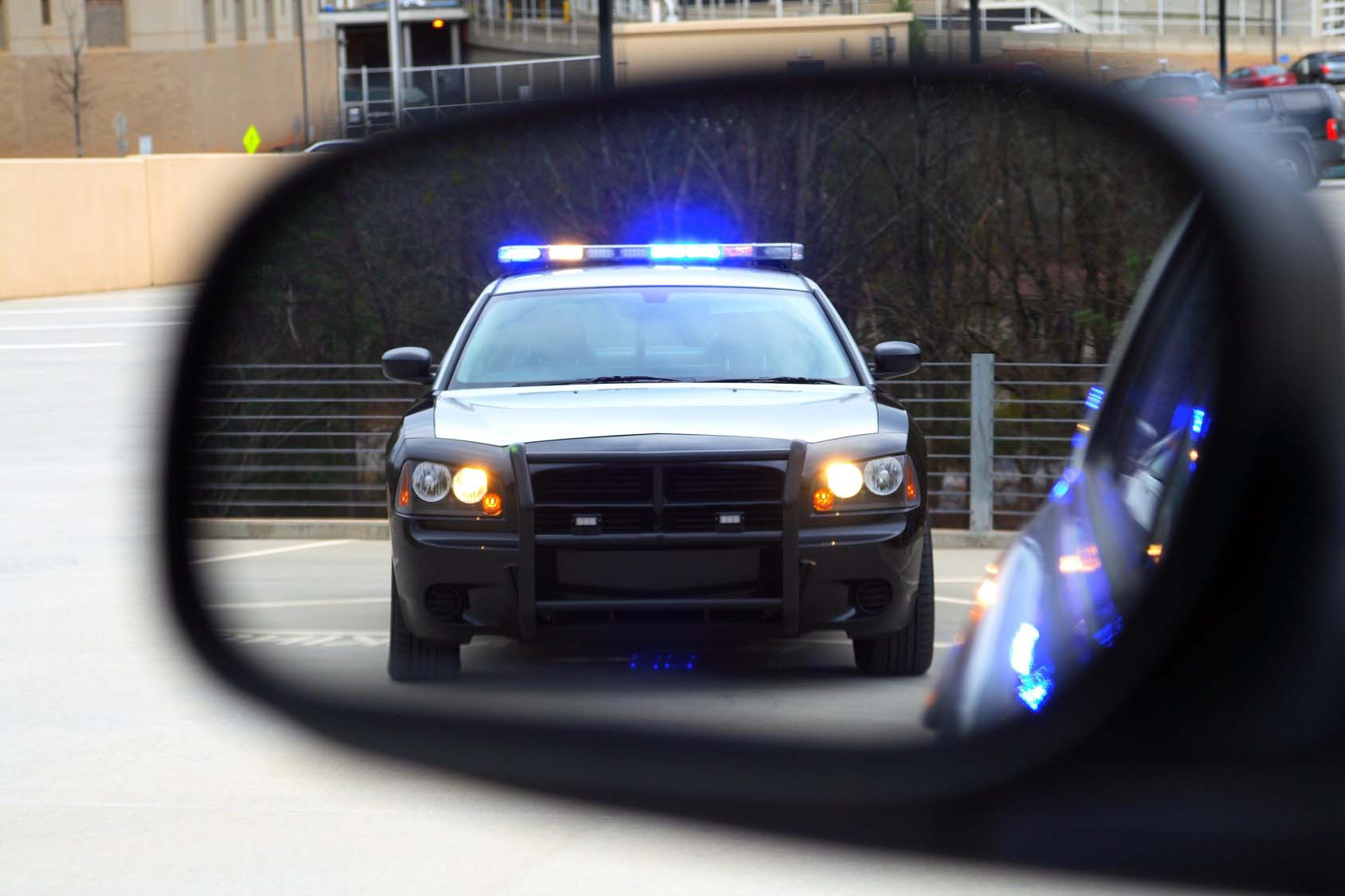 police car in a rear view mirror